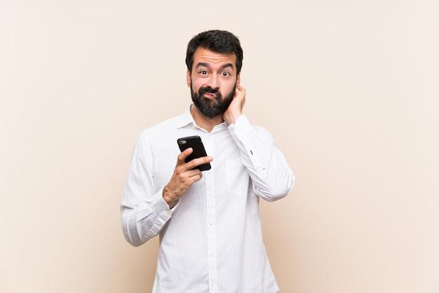 疑いのある携帯電話を保持しているひげを持つ若者