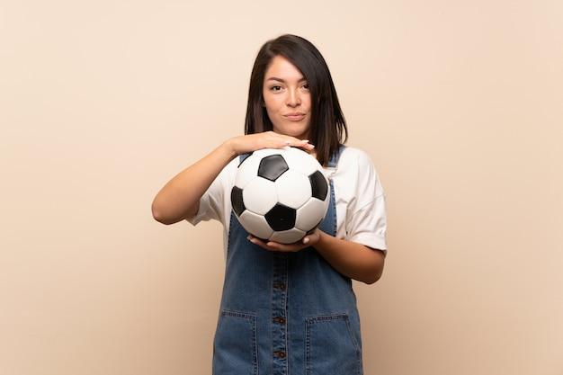 Молодая мексиканская женщина над изолированным держащ футбольный мяч