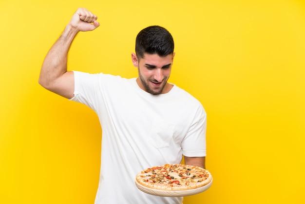 Молодой красивый мужчина держит пиццу над желтой стене, празднующей победу