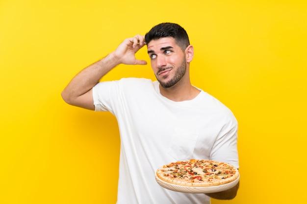 Молодой красавец, держа пиццу на изолированных желтой стене, с сомнениями и с выражением лица смутить