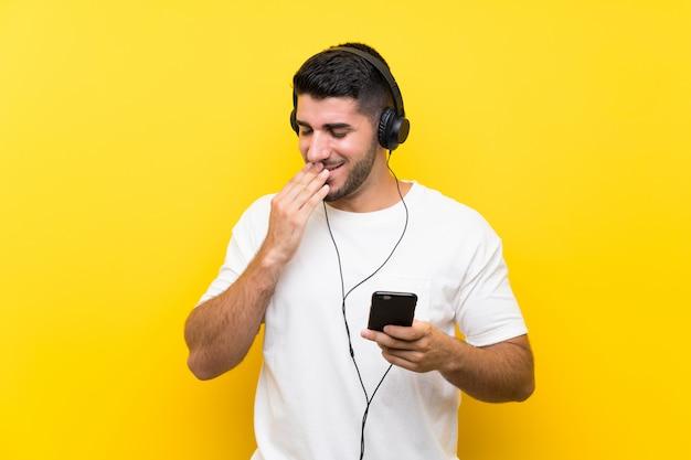 多くの笑みを浮かべて孤立した黄色の壁を越えて携帯電話で音楽を聴く若いハンサムな男