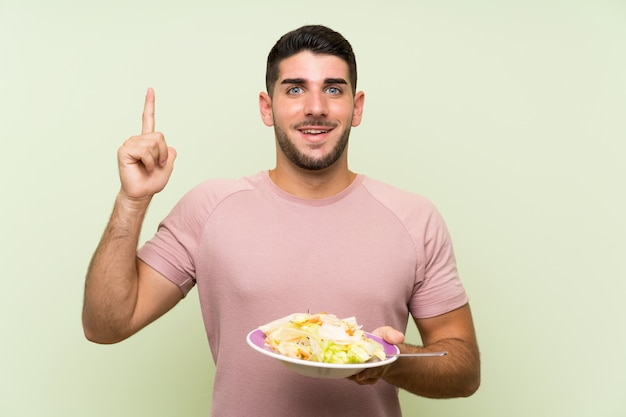 素晴らしいアイデアを指している孤立した緑の壁の上のサラダと若いハンサムな男