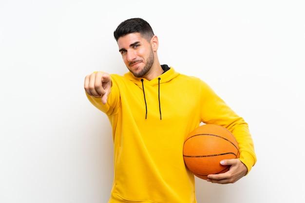 孤立した白い壁の上のハンサムな若いバスケットボールプレーヤー男は自信を持って表現であなたに指を指す