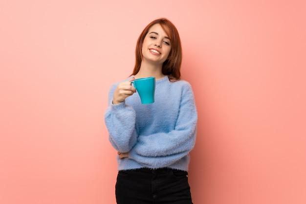 熱い一杯のコーヒーを保持しているピンクの上の若い赤毛の女性