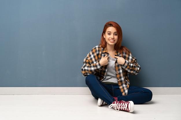 驚きの表情で床に座っている若い赤毛の女性