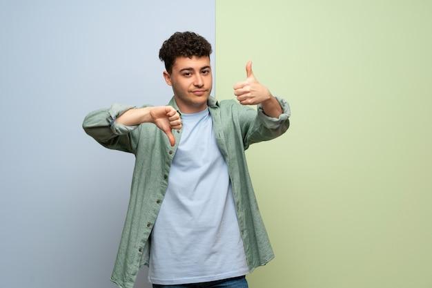 青と緑の良い悪いサインを作る若い男。はいかどうかは未定