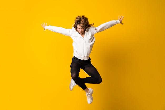 黄色の壁にジャンプする若い女性