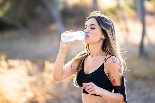 公園内の水のボトルを持つ若いスポーツ女性