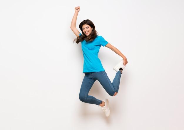 ティーンエイジャーの女の子が白い壁をジャンプ