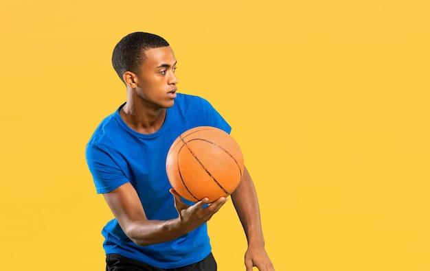 孤立した黄色の上のアフロアメリカンバスケットボールプレーヤー男