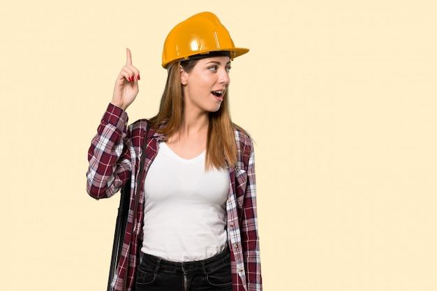孤立した黄色の上に指を持ち上げながらソリューションを実現しようとしている建築家の女性