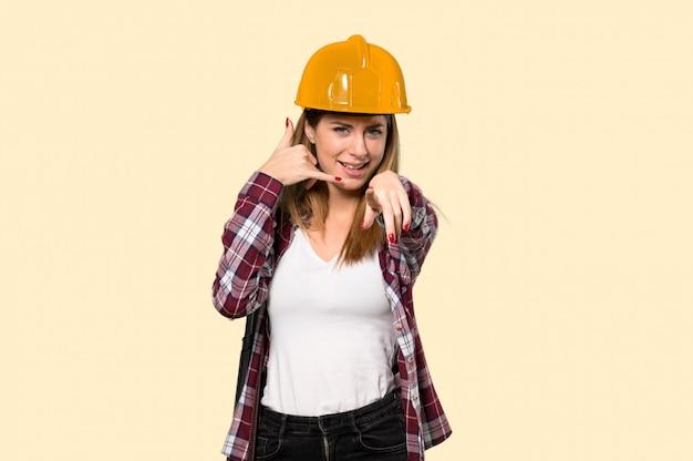 建築家の女性電話ジェスチャーを作ると孤立した黄色の上の前面を指す