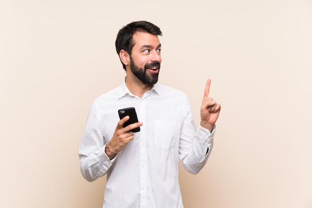 指を上向きにするアイデアを考えてモバイルを保持しているひげを持つ若者