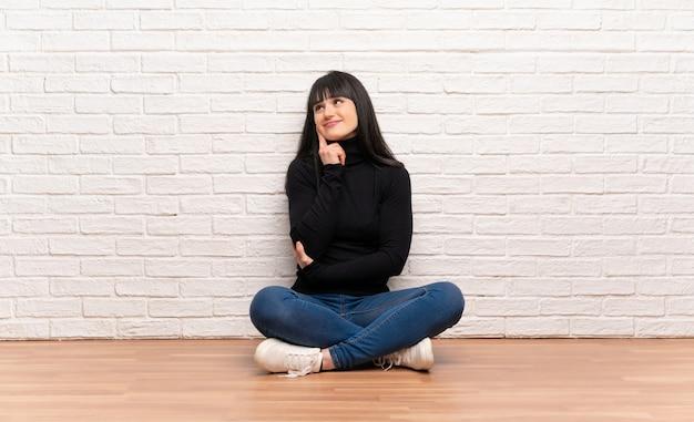 見上げながらアイデアを考えて床に座っている女性