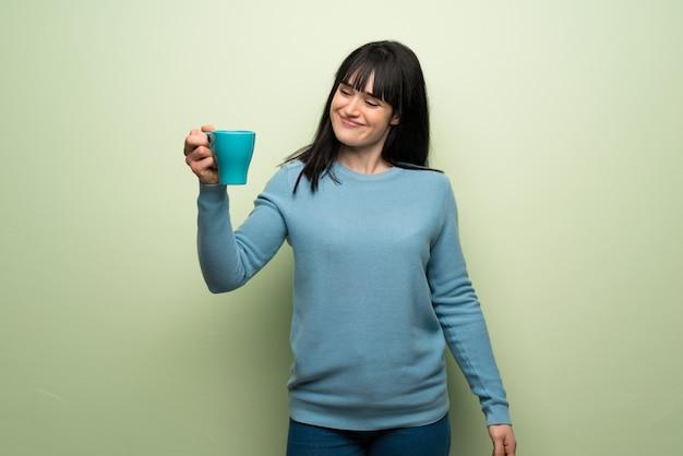 熱い一杯のコーヒーを保持している緑の壁に若い女性