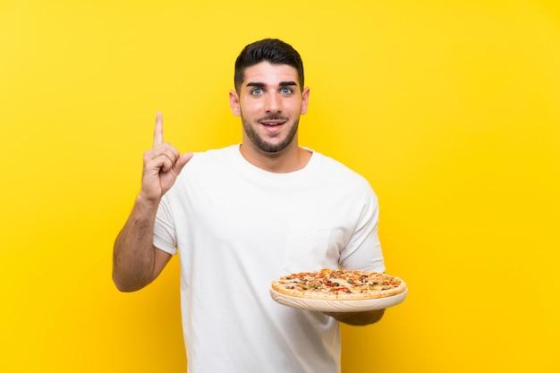 Молодой красивый мужчина держит пиццу на желтой стене, указывая отличная идея