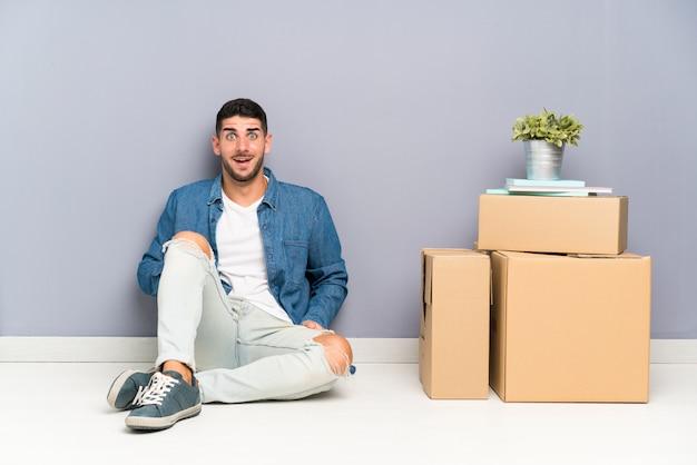 驚きの表情を持つボックスの間で新しい家に移動するハンサムな若い男