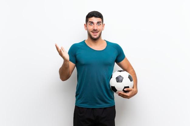 ショックを受けた表情で白い壁にハンサムな若いフットボール選手男