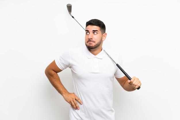 白のハンサムな若いゴルファープレーヤー男の肩を持ち上げながら疑いジェスチャーを作る