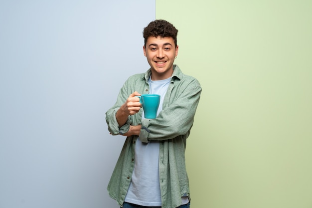 青と緑の熱い一杯のコーヒーを保持している以上の若い男