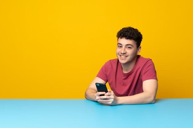 カラフルな壁とテーブルで携帯電話でメッセージを送信する若い男