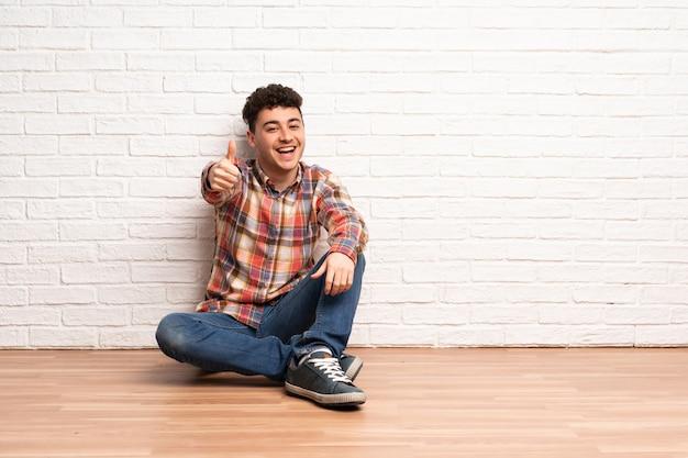 何か良いことが起こったため、親指で床に座っている若い男
