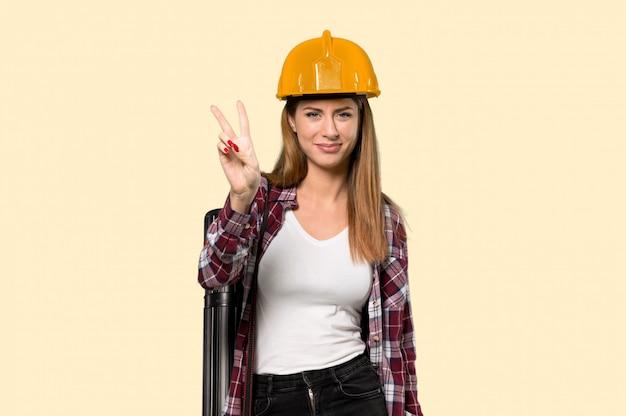 笑みを浮かべて、黄色の勝利のサインを示す建築家女性