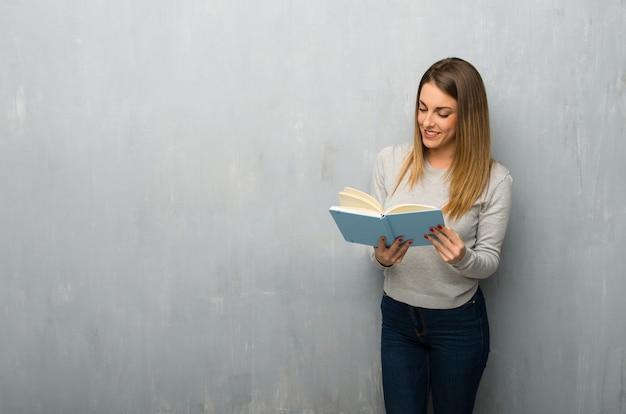 本を持って、読書を楽しんでテクスチャ壁の若い女性