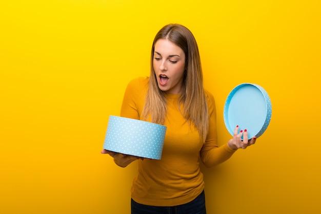 手でギフト用の箱を保持している黄色の若い女性