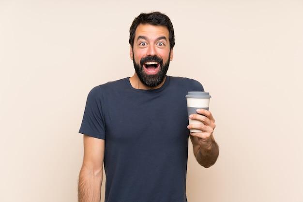Человек с бородой держит кофе с удивлением и шокирован выражением лица