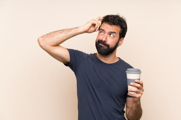 Человек с бородой, держа кофе с сомнением и смущенным выражением лица