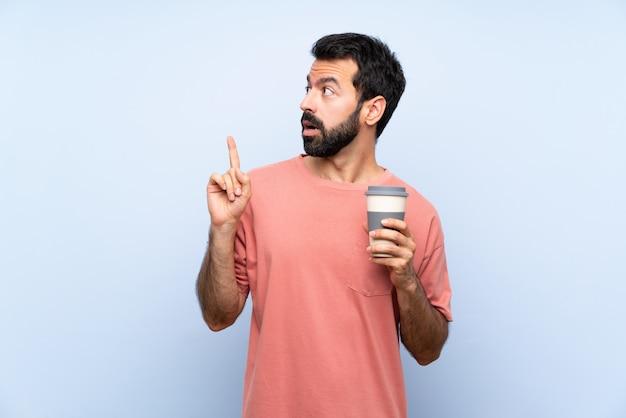 Молодой человек с бородой, держа прочь кофе на изолированных синий мышления идея, указывая пальцем вверх