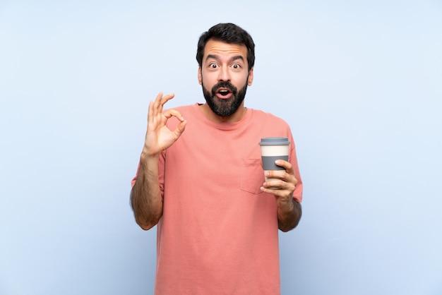Молодой человек с бородой, держа прочь кофе на изолированных синий удивлен и показывает знак ок