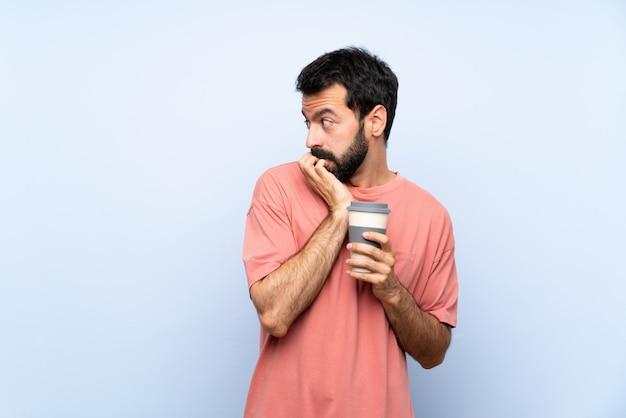 Молодой человек с бородой, держа кофе на вынос за изолированные синий нервной и страшно положить руки в рот