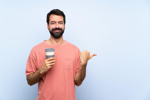 製品を提示する側を指している孤立した青い壁にテイクアウトコーヒーを保持しているひげを持つ若者