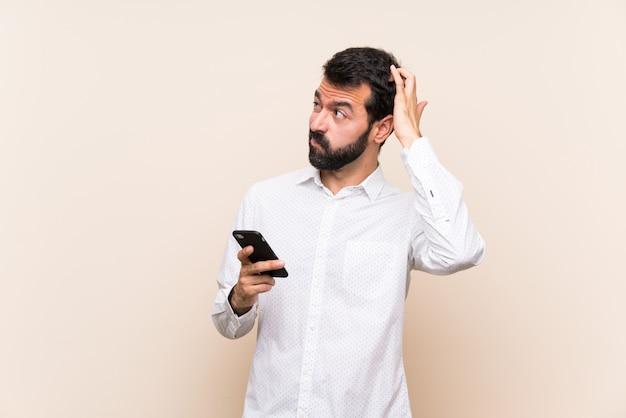 頭をかきながら疑問を持つ携帯を保持しているひげを持つ若者