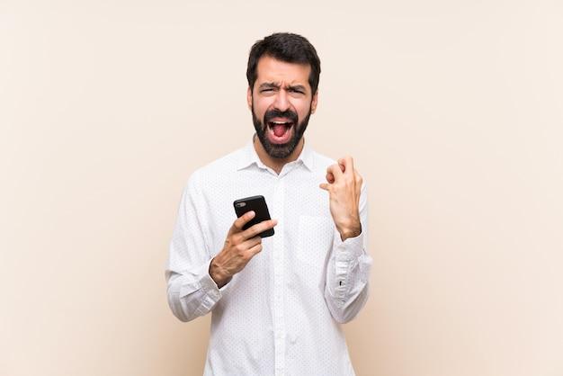 悪い状況に不満の携帯を保持しているひげを持つ若者