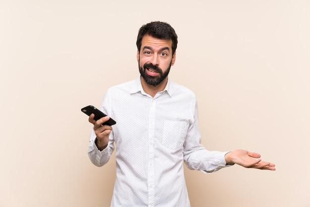 何かを理解していないために不幸な携帯電話を保持しているひげを持つ若者