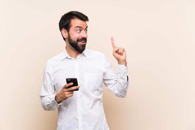 指を持ち上げながら解決策を実現するつもりの携帯電話を保持しているひげを持つ若者