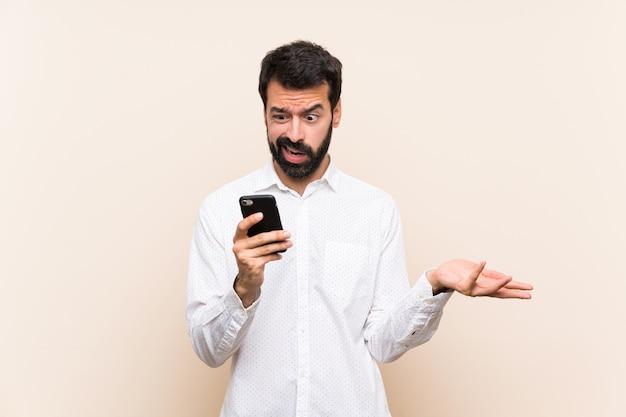 疑いジェスチャーを作る携帯電話を保持しているひげを持つ若者