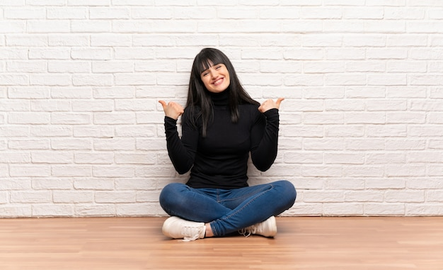 ジェスチャーを親指を与えると笑顔の床に座っている女性