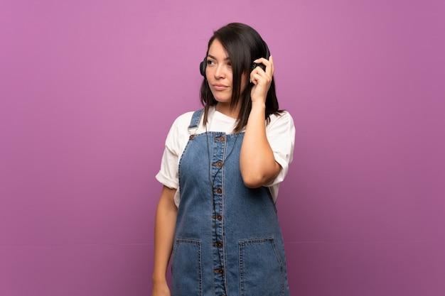 ヘッドフォンで音楽を聞いて孤立した壁の上の若いメキシコ人女性