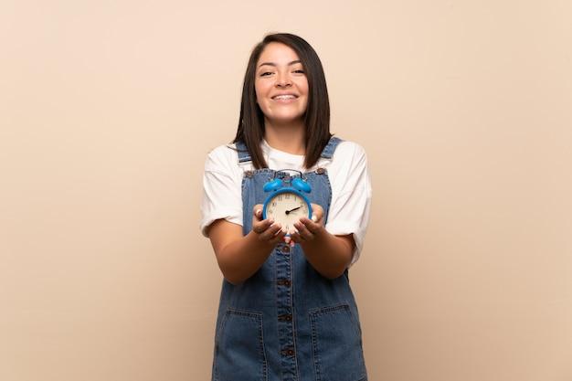 ビンテージの目覚まし時計を保持している孤立した壁の上の若いメキシコ人女性
