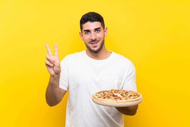 Молодой красивый мужчина держит пиццу над желтой стене, улыбаясь и показывая знак победы