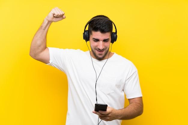 勝利を祝う孤立した黄色の壁の上の携帯電話で音楽を聴く若いハンサムな男