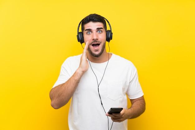 驚きとショックを受けた表情で孤立した黄色の壁を越えて携帯電話で音楽を聴く若いハンサムな男