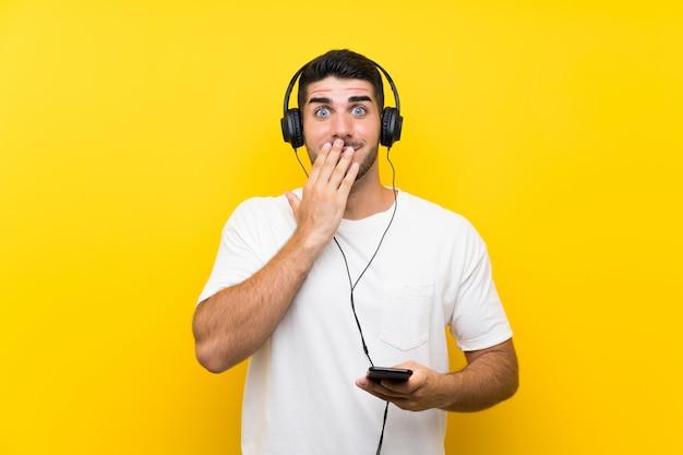驚きの表情で孤立した黄色の壁を越えて携帯電話で音楽を聴く若いハンサムな男