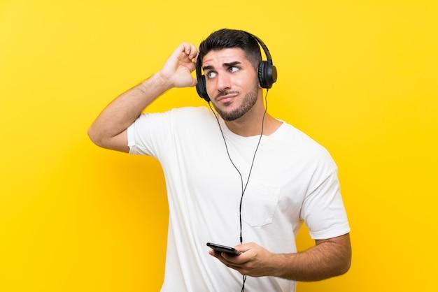 若いハンサムな男が疑問を持っている孤立した黄色の壁を越えて携帯電話で音楽を聞き、表情を混乱させる