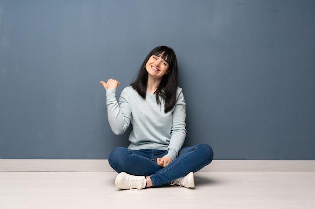製品を提示する側を指している床に座っている女性