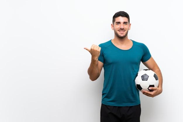 製品を提示する側を指している孤立した白い壁の上のハンサムな若いフットボール選手男